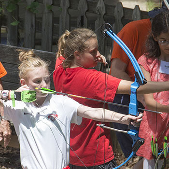 Two young women aiming arrows at summer archery at IWLA-R