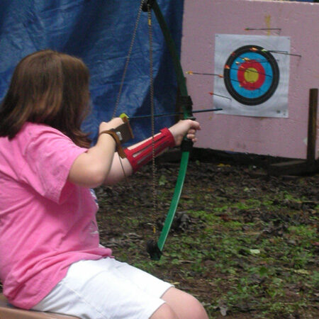 Mary C. aiming at a target at an archery session